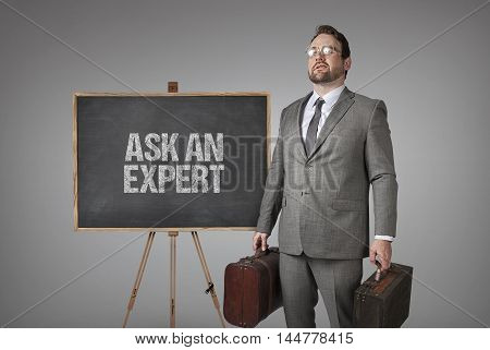 Ask an expert text on  blackboard with businessman carrying suitcases