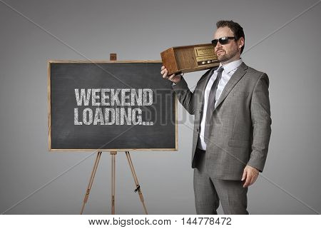 Weekend loading text on blackboard with businessman holding radio