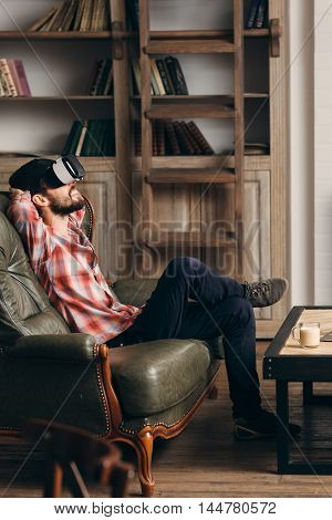 Young bearded man enjoying virtual reality glasses. Relaxed smiling guy in vr headset watching movie at home. Innovation, modern technology, rest, cyberspace, entertainment concept