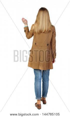 Back view of beautiful woman welcomes. blonde in a brown cloak is waving.