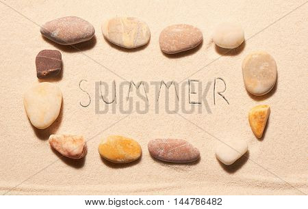 Frame Of Sea Stones With Summer Lettering Drawn On Sand