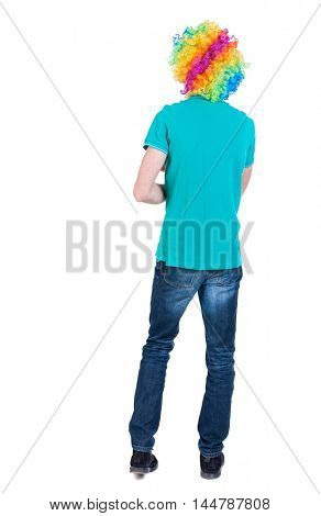 back view of dancing young beautiful man in clown wig. Curly man in a turquoise sweater and clown wig