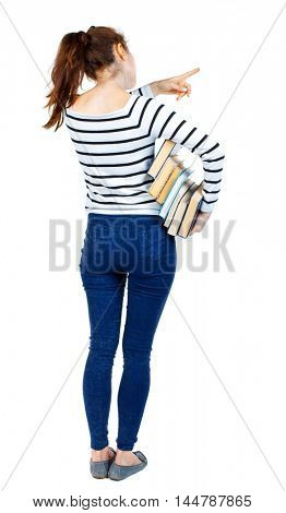 Girl with a stack of books points the finger. back side view. Girl in striped sweater holding a stack of books under his arm and pointing up with a finger.