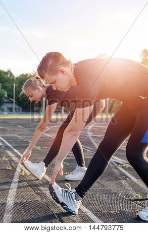 Young cute woman and man stretching their legs before running or fitness workout outdoors.