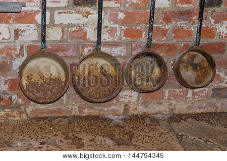 Old rusty foundry ladles hanging on a wall of bricks.