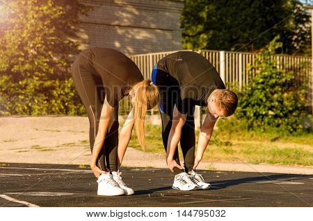 Young caucasian man and woman in sportswear stretching bodies before fitness or running workout.