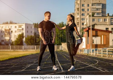 Young attractive teens doing warming up exercises before workout outdoors.