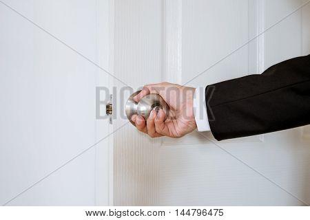 Businessman hand holding door knob, opening or closing door, with bright behind the door