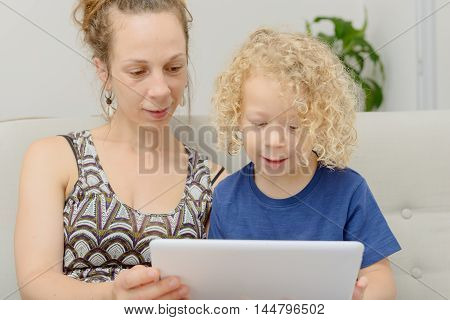 a blond little boy and his mom with a digital tablet