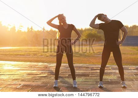 Young healthy caucasian man and woman warming up outdoors before fitness or running workout.