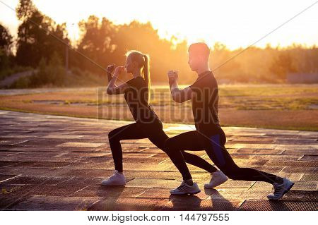 Two silhouettes of fit young man and woman doing lunges outdoors at sunset. Fitness or running workout outdoors