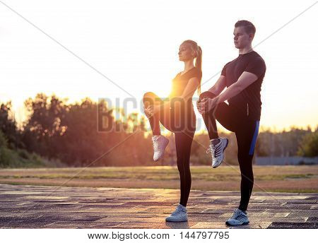 Young caucasian man and woman warming up before exercising or jogging outdoors. Fitness workout.