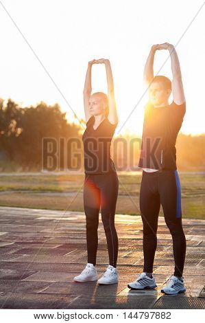 Young adults couple warming up, stretching arms before running or jogging. Fitness workout outdoors.