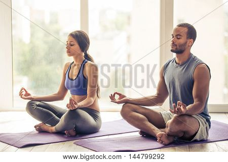 Beautiful Afro American couple in sports clothes is meditating sitting in lotus position on mat while doing yoga at home poster