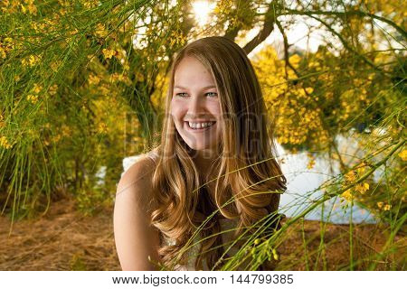 A teenage girl sits looking off into the distance. She is surrounded by yellow palo verde flowers in late afternoon sunlight and looks radiant.