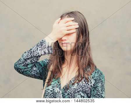 facepalm girl. Portrait of young woman doing facepalm posing against gray wall background