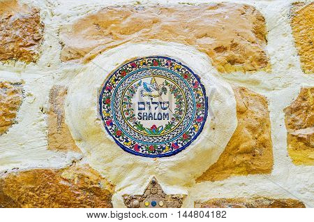 SAFED ISRAEL - FEBRUARY 22 2016: The house wall decorated with the circle porcelain tile with the peace dove and colorful floral pattern on February 22 in Safed.