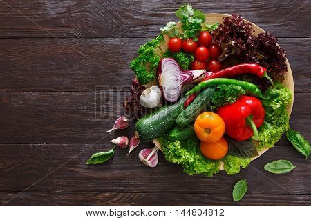 Dish with fresh organic vegetables on wood background. Healthy natural food abundance on rustic wooden table with copy space. Tomato, lettuce, onion, pepper and other cooking ingredients top view