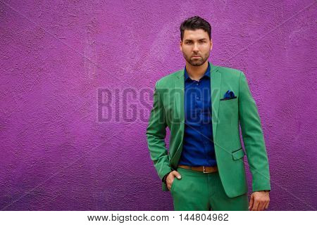 Man in green suit and blue shirt looking at camera