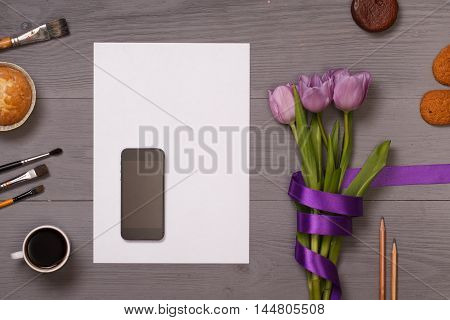 Banner template layout mockup for woman day, Valentine's Day and Teachers' Day. White wooden table, top view on workplace. Lilac tulips at the Desk. View from above with copy space.