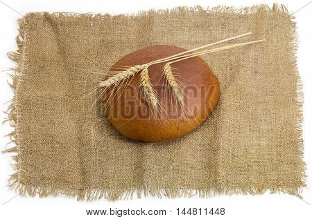 Round loaf of wheat rye hearth brown bread and three wheat spikes on a sackcloth on a light background