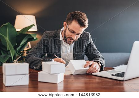 Young entrepreneur sitting at a table at home next to a laptop writing addresses on packages for delivery to customers