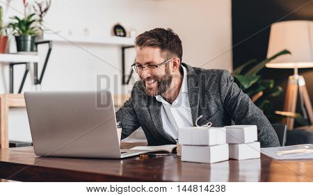 Smiling young entrepreneur working on a laptop while sitting at table at home with boxes ready for deliver to customers