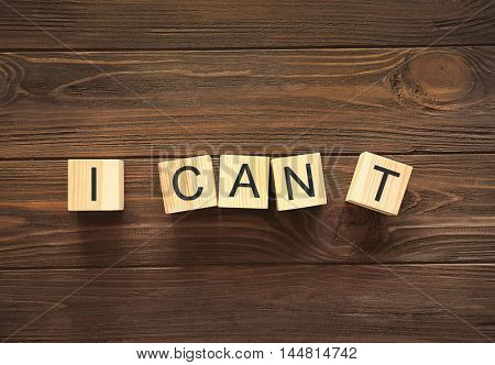 Cubes with phrase I CANT on wooden background