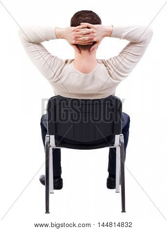 back view of business man sitting on chair. bearded man in a white warm sweater sits on a chair thrown at his head.