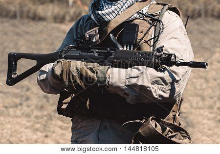 A soldier wearing a vest holding an assault rifle.
