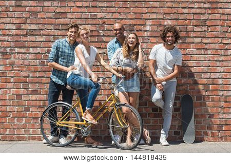 Cheerful group of friends enjoying summer vacation. Happy young couples and friends having fun together and looking at camera. Young men and smiling girls leaning against a brick wall.