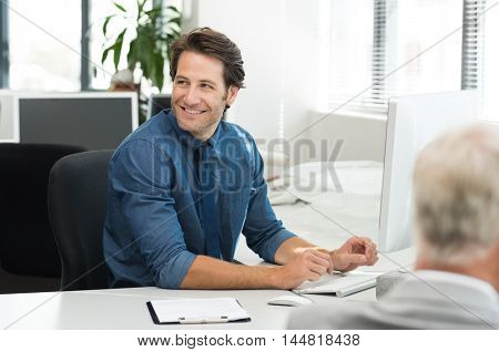 Cheerful young businessman working on desktop computer at office. Happy smiling business man looking away while working in office. Cheerful man sitting at desk in a co-work office.
