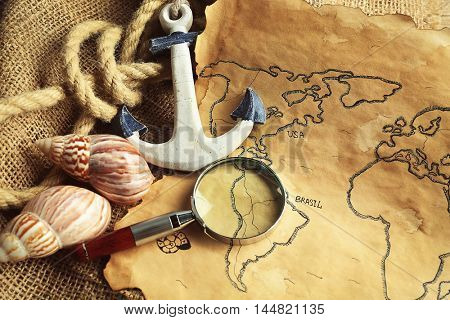 Magnifier, anchor and seashells on old map. Happy Columbus day concept
