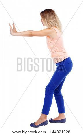 back view of woman pushes wall. Isolated over white background. Blonde in blue pants shoves it to the side.