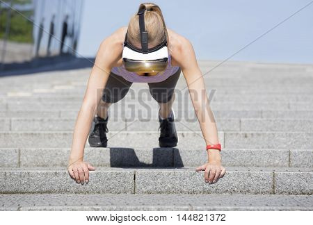 Sportive and beautiful woman makes her pushup workout on stairs wearing virtual reality glasses which show a nature scene and fitness data. A red fitness tracker is located on her left arm.