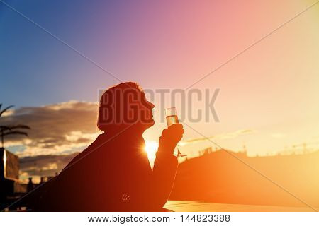 Silhouette of young man drinking wine in city at sunset