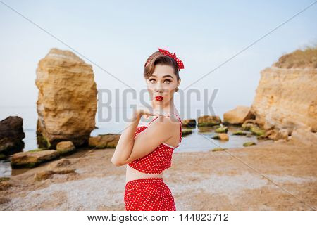 Happy pretty pinup girl in red swimsuit sending a kiss standing at the beach
