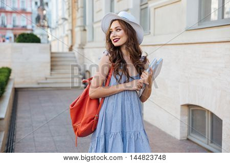 Cheeful attractive young woman with red backpack and book walking in the city