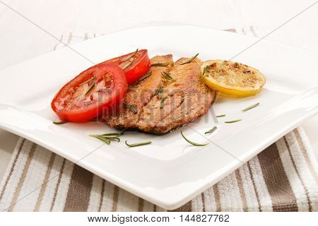 grilled scottish kipper with rosemary tomato and slice lemon an a white plate