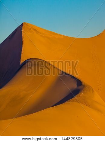Mesquite Flat Sand Dunes. Bright sunny morning in a picturesque part of Death Valley, USA. Bizarre twists of orange sand dunes