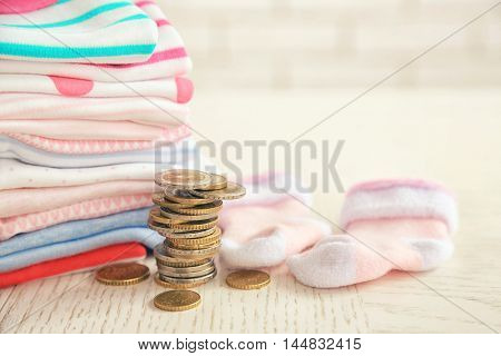 Parenting expenses concept. Pile of baby clothes and coins