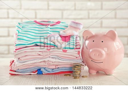 Parenting expenses concept. Pile of baby clothes and piggy bank