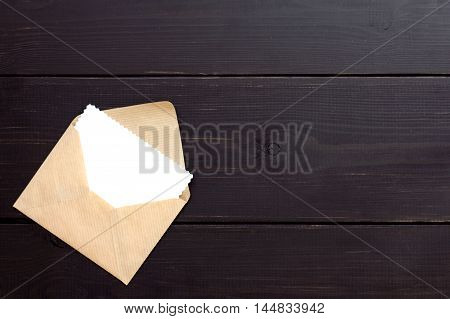 envelope with looking out his blank form lying on dark wooden background top view / post envelope with a letter