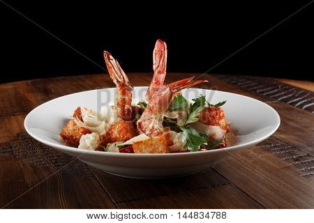 Caesar salad with king prawns in a white plate. Salad with shrimp on wooden brown background.