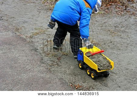 Children's outdoor play. Child in a blue jacket boots gloves hat and black pants plays with toy machine. The boy pulls the loaded sand machine behind the hill.