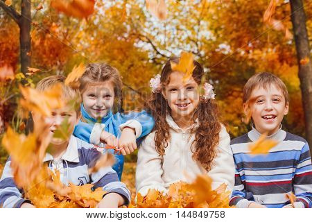Cheerful group of kids of school age playing with yellow leaves in an autumn park