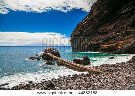 people waiting for the transfer to Los Gigantes at the Playa de Masca at the end of the popular Gorge walk Tenerife Canary islands Spain