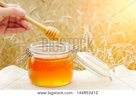 Aromatic fragrant fresh honey poured in a glass the viscosity of honey with the help of hands and a special spoon.