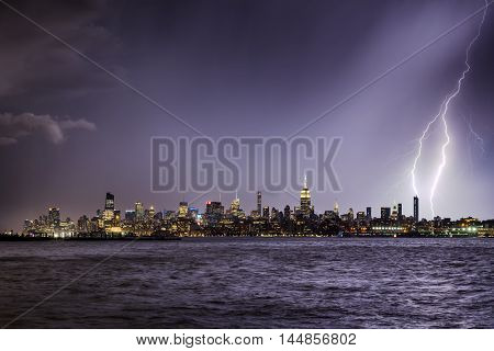 Lightning hitting a New York City skyscraper at twilight. Stormy skies over Midtown West Manhattan from the Hudson River