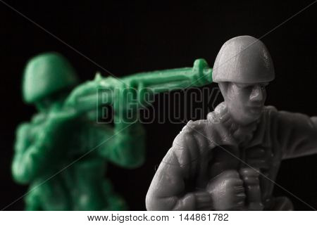 Green toy soldier surprises enemy from behind